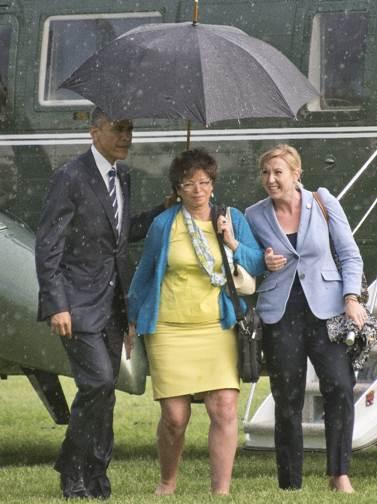 Obama, caballero antes que presidente; cubre a mujeres de lluvia